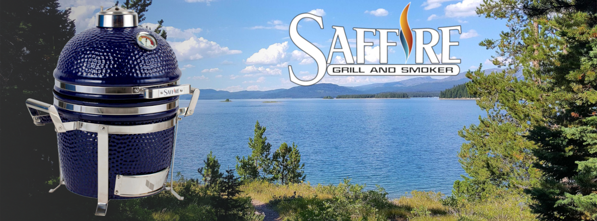 The portable 13 inch Saffire kamado is shown with a lake background and the lid closed.