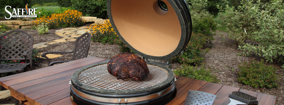 A beautifully-cooked pork rump is shown on an open Saffire ceramic grill, with a nice garden backdrop