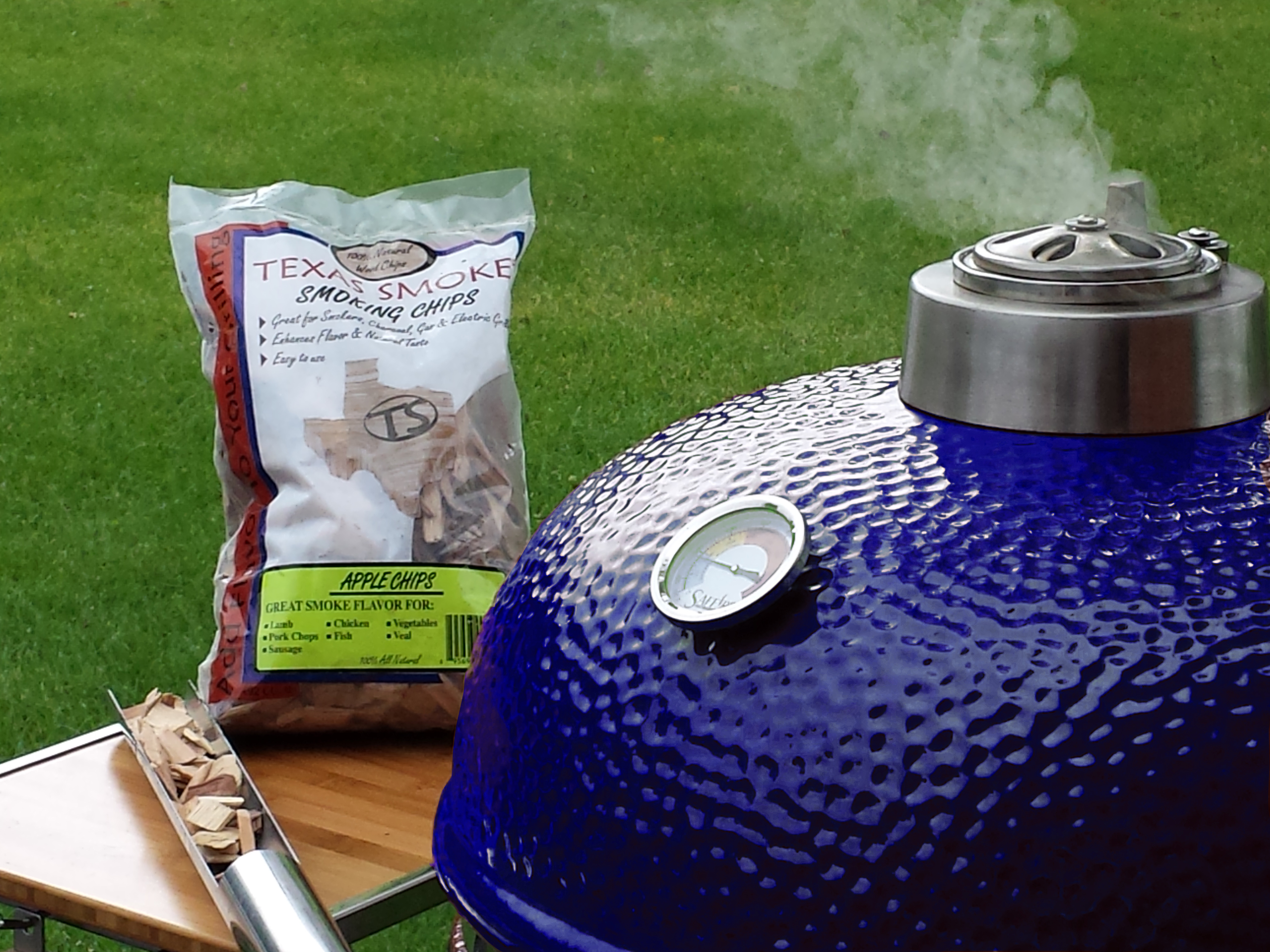 A blue Saffire kamado with steam coming out the top and a bag of wood chips and the smokin' chip feeder tool on the grill's side shelf