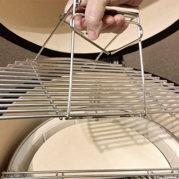 A grid lifter is shown holding up half of a two-piece cooking grid for easy removal or placement during a cook-out