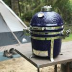 The 13 inch small Saffire ceramic grill sits on a camping table. In the background is a tent and boots sitting on a mat outside the tent.