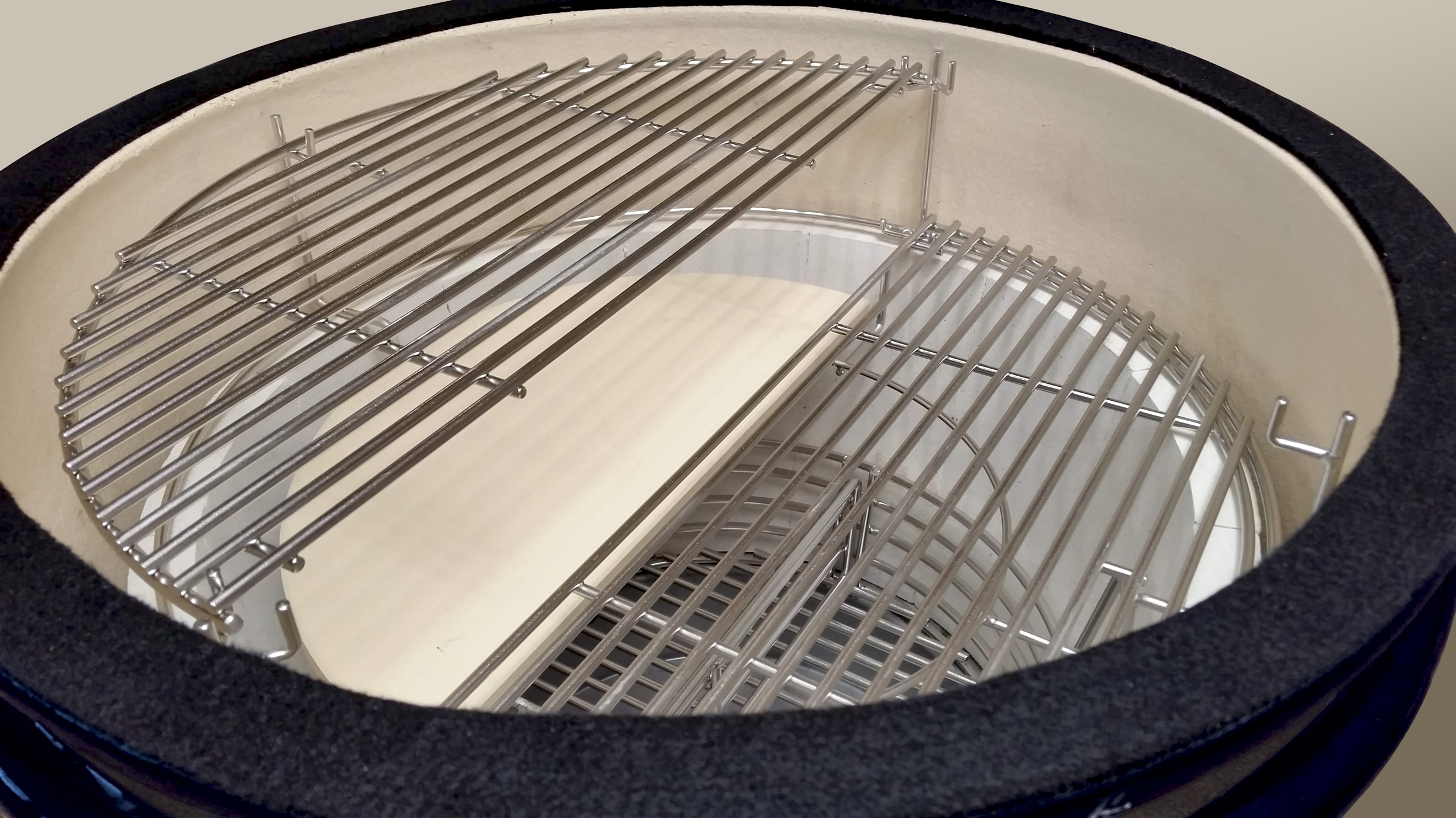 The multi level cooking system is shown with one grid at the top and one grid at the bottom; a half two piece heat deflector piece is below the grid sitting at the top of the system