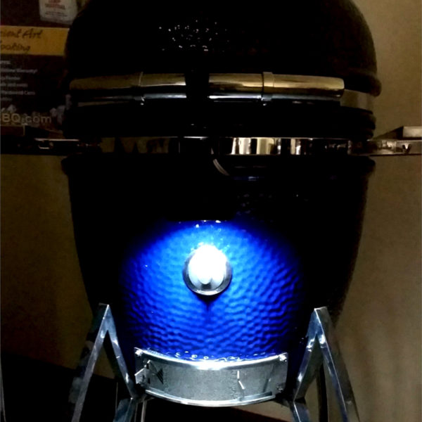 A GL-320 Maverick grill light is shown mounted to a Saffire so that the light shines down on the smoking chip feeder port when the grill is closed